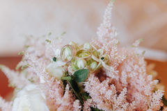 Closeup shot of wedding rings on a pink floral bouquet Royalty Free Stock Photography