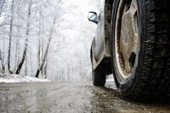 Closeup shot of wheel on the snow road. White trees on background royalty free stock images