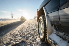 Closeup shot of wheel on the snow road. One more car in morning light ride by the road stock images