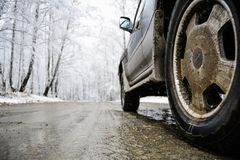 Closeup shot of wheel on the snow road. White trees on background stock images