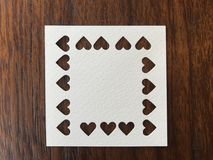 """Closeup shot of white square blank paper which was punched in heart shape. In the middle of dark brown wood table, `valentine`s day"""" concept Royalty Free Stock Photo"""