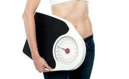 Closeup shot, woman carrying weighing machine Royalty Free Stock Photography