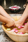 Closeup shot of a woman feet dipped in water with petals in a wooden bowl. Royalty Free Stock Images