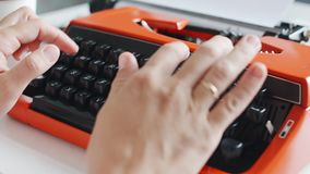 Woman hand typing on red vintage typewriter. Closeup shot of woman hand typing on red vintage typewriter stock video footage