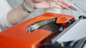 Woman hand typing on red vintage typewriter. Closeup shot of woman hand typing on red vintage typewriter stock footage