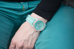 Closeup shot of a woman hand with watch. In teal blue color Royalty Free Stock Photo