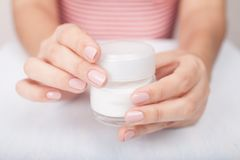 Closeup shot of woman hands applying moisturizing hand cream royalty free stock image