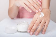 Closeup shot of woman hands applying moisturizing hand cream royalty free stock photo