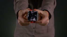 Closeup shot of woman hands holding a small gift box wrapped with grey ribbon stock footage