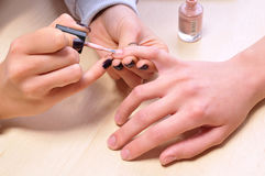 Closeup shot of woman in a nail salon. Receiving a manicure by a beautician Royalty Free Stock Photos