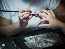 Woman in a nail salon receiving a manicure by a beautician with nail file woman Royalty Free Stock Photo