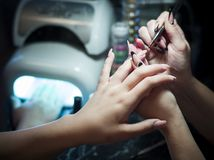 Woman in a nail salon receiving a manicure by a beautician with nail file woman Royalty Free Stock Photography