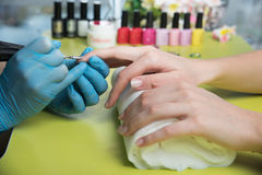 Closeup shot of a woman in a nail salon receiving a manicure by a beautician with nail file. Woman getting nail manicure Stock Image