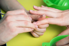 Closeup shot of a woman in a nail salon receiving a manicure by a beautician with nail file. Woman getting nail manicure Royalty Free Stock Photography