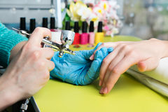 Closeup shot of a woman in a nail salon receiving a manicure by a beautician with nail file. Woman getting nail manicure Royalty Free Stock Photos