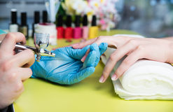 Closeup shot of a woman in a nail salon receiving a manicure by a beautician with nail file. Woman getting nail manicure Royalty Free Stock Images