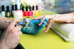 Closeup shot of a woman in a nail salon receiving a manicure by a beautician with nail file. Woman getting nail manicure Royalty Free Stock Image