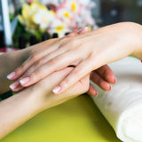 Closeup shot of a woman in a nail salon receiving a manicure by a beautician with nail file. Woman getting nail manicure Stock Images
