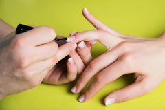 Closeup shot of a woman in a nail salon receiving a manicure by a beautician with nail file. Woman getting nail manicure Royalty Free Stock Photo