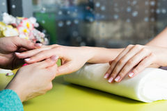 Closeup shot of a woman in a nail salon receiving a manicure by a beautician with nail file. Woman getting nail manicure Stock Photography