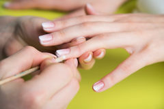 Closeup shot of a woman in a nail salon receiving a manicure by a beautician with nail file. Woman getting nail manicure. Beautici Royalty Free Stock Image