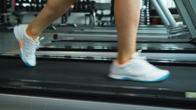Closeup shot of woman`s legs running on treadmill at the gym. Fitness club. Health, sport and cardio workout concept stock video footage