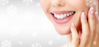 Closeup shot of woman`s toothy smile. Against a grey background with snowflakes Stock Image