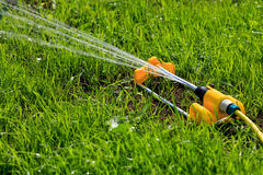 Yellow lawn sprinkler spaying water Royalty Free Stock Image