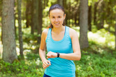 Closeup shot of young female runner ready to run with sports sma Royalty Free Stock Photo