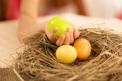 Closeup shot of young girl taking green Easter egg from the nest Stock Images