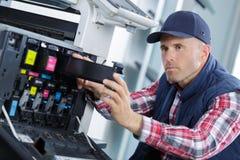 Closeup shot young male technician repairing digital photocopier machine. Male Stock Photos
