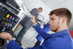 Closeup shot young male technician repairing digital photocopier machine. Teen Stock Photography