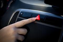 Closeup shot of young woman pressing emergency button in car Stock Photos