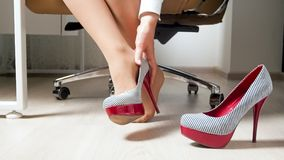 Closeup shot of young woman taking high heels shoes in office stock photos