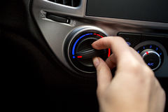 Closeup shot of young woman turning car air conditioner switch Stock Photo