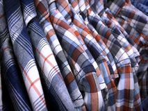 Patterned Shirts for Men Hanging on Rack in Clothing Store. Closeup Shoulder of Patterned Shirts for Men Hanging on Rack in Clothing Store Stock Photos