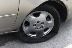 Car with flat shredded tire. Closeup of shredded flat tire on car Stock Photos