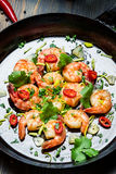 Closeup of shrimps on pan with fresh herbs Stock Photo