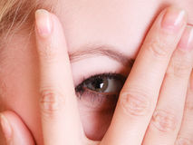 Closeup shy afraid woman peeking through fingers Royalty Free Stock Photos