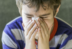 Closeup of sick boy in pyjamas sneezing into a tissue, health co Royalty Free Stock Photo