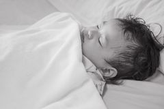 Closeup sick child sleep on hospital bed textured background in black and white tone Stock Images