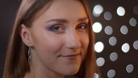 Closeup side portrait of young pretty caucasian girl turning and looking at camera smiling with bokeh lights on the stock video footage