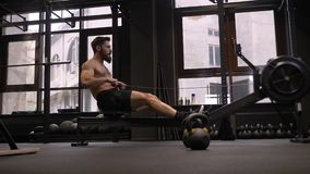 Closeup side view of adult motivated athletic shirtless man using rowing machine and making resistance training in the. Gym stock video footage