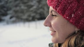 Closeup Side View Face Woman In Winter On The Street Looking Into The Distance. Side view of a closeup face of a young Caucasian woman, she is in the winter on stock footage