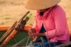 Closeup Side View Woman in Hat Repairs Fishing Net in Round Boat Royalty Free Stock Image