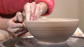 Closeup side view of a muddy hands fine-tuning a clayware shape on the spinning potter`s wheel.