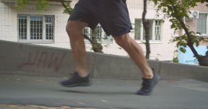 Closeup side view portrait of adult determined sporty male runner jogging up the stairs on the street in the urban city stock video