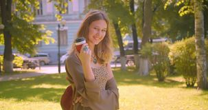Closeup side view portrait of young cute caucasian female looking at camera drinking coffee smiling happily standing in. Park outdoors stock footage