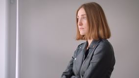 Closeup side view portrait of young cute caucasian girl in a leather jacket having her arms crossed looking at camera. Indoors in the empty room stock footage