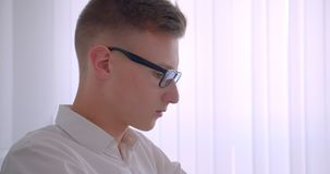 Closeup side view portrait of young handsome caucasian businessman in glasses turning to camera indoors in a white room.  stock video footage